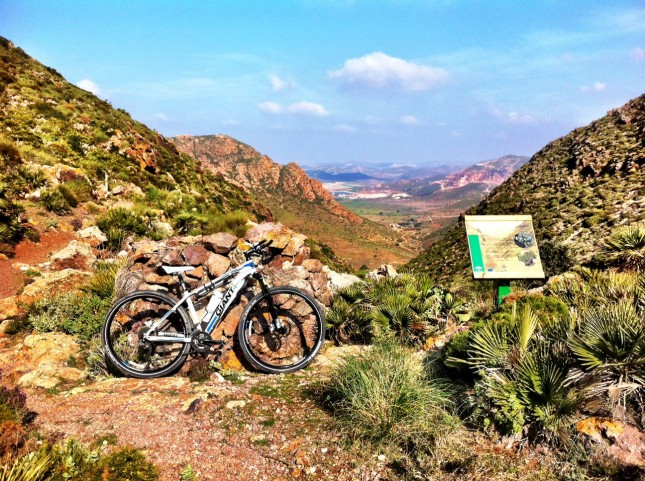 The bike propped against a stone hunting shelter/bunker, an information board outlining some of the local flora, and a rocky path!